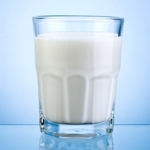 Glass of fresh milk isolated on blue background